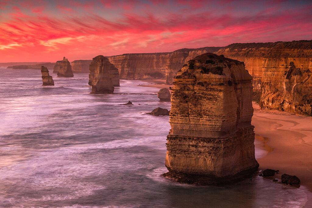 Port Campbell, Australia. Sunset at The Twelve Apostles monument near Port Campbell National Park, Victoria, Australia, on this particular summer evening seemed to be a game of cat-and-mouse. The sky went from being perfectly clear in the northwest to seeing some wispy clouds roll in just before the sun sank to the horizon. Then it happened – passion in the sky that was reflected back onto the terrain. It went from orange to pink to red and then to a dull ashen gray as the fire in the sky burned itself out. It was an unforgettable evening on the Southern Ocean in the underbelly of the Australian continent along the Great Ocean Road. Canon 5D Mark III w/Canon 24-105 f/4L IS USM. Exposure: v focal length 58mm/ f/22/ 2.5 seconds/ ISO 200.