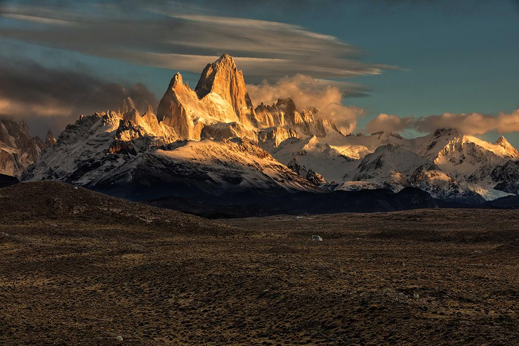 Los Glaciares National Park, Argentina. Mt. Fitzroy bathed in golden light of sunrise outside El Chalten, Patagonia, Argentina. Patagonia is a long way away from where I live in the Pacific Northwest of the USA, so when you get to an iconic photography location like this, you are naturally keeping your hopes up that weather conditions will cooperate. On our first two attempts to photograph sunrise at this location, we were disappointed by the cloud cover snuffing out any hope of seeing Fitzroy. But on the third morning, with our bags packed and ready to go, we drove out to this location and were treated to a beautiful sunrise, with dispersing rain clouds that made everything even more dramatic. Canon 5DsR, Canon 70-200mm f/2.8 L IS USM. Exposure: f/16, ISO 200, 1/16 second.