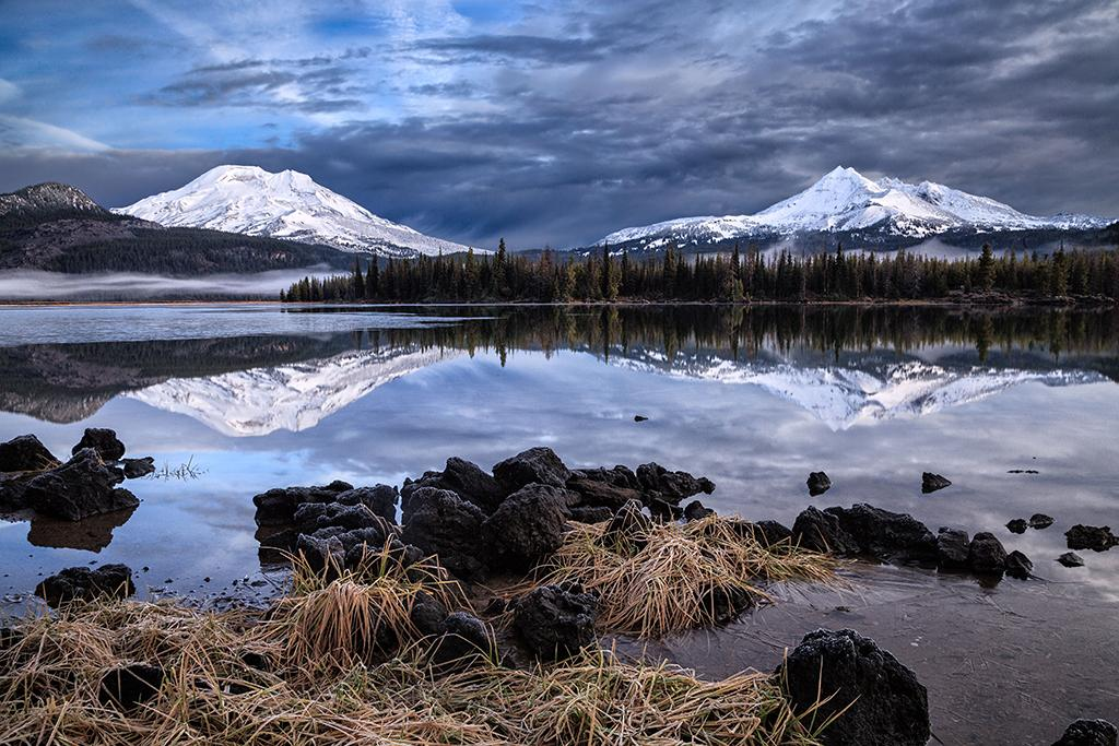 Sparks Lake, Oregon. I was waiting for the first snow of the season to dust the mountains (South Sister and Broken Top) visible from Sparks Lake in the Cascade Range of Oregon. When I saw the overnight forecast calling for snow in the higher elevations, I knew I'd be getting up early to make the 40 minute drive to the alpine lake. The only question was whether the road would be closed by the highway department due to the snow. To my delight, the road remained open and I was able to make it back to the lake well before dawn. Exposure: f/22, ISO 100, 0.6 second.